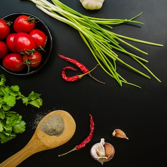 Overhead view of tomato; red chilies; spring onion; garlic; parsley and spices over black background
