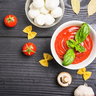An overhead view of tomato sauce with mozzarella; pasta; mushroom and garlic
