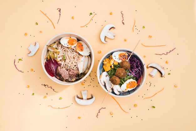 An overhead view of traditional asian cuisine bowls decorated with mushroom and sesame seeds on colored backdrop