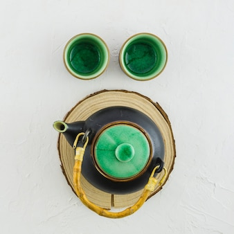 An overhead view of traditional teapot and two cups on white background
