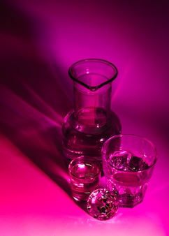 An overhead view of transparent glasses; beaker and diamond on dark pink background