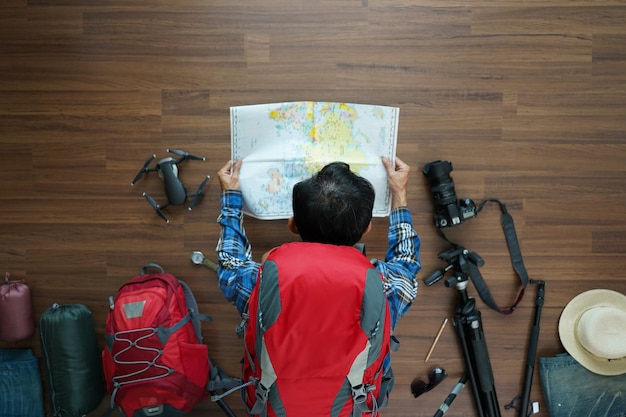 Overhead view of traveler man plan and backpack with map