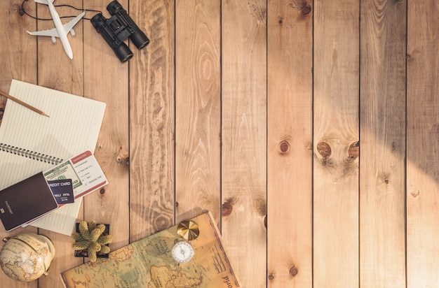 Overhead view of traveler's accessories essential vacation items, and different objects on wooden wall. travel concept wall