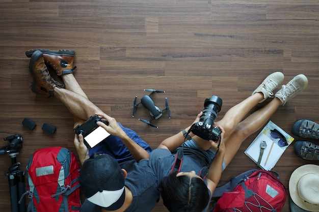 Overhead view of traveler's young couple planning with holding camera with drone