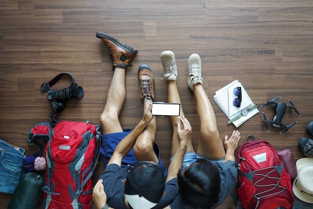 Overhead view of traveler's young couple planning with holding smart phone