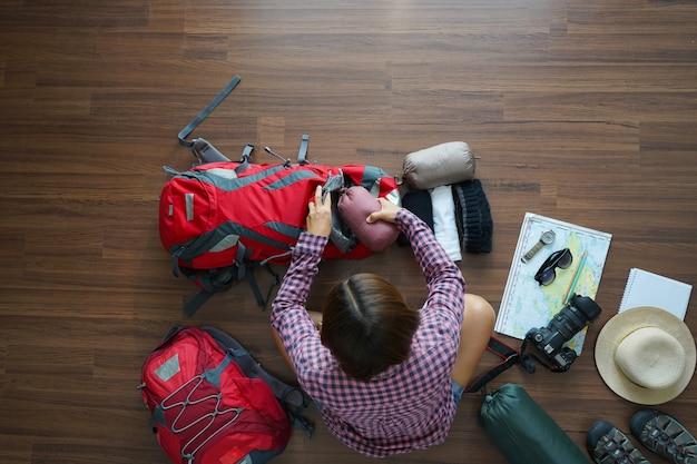 Overhead view of traveler woman plan and backpack planning