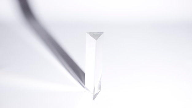 An overhead view of triangular prism with dark shadow on white background
