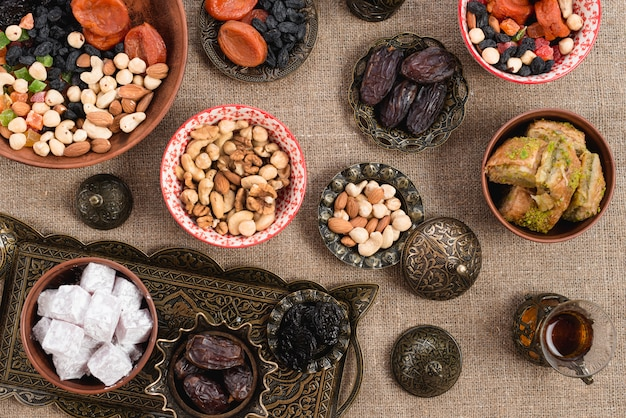 An overhead view of turkish tea; dates; lukum; dried fruits and nuts on jute tablecloth