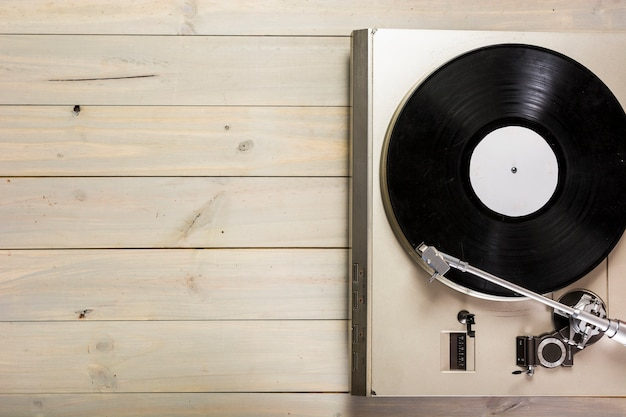 An overhead view of turntable vinyl record player on wooden table