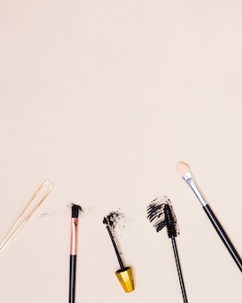 An overhead view of tweezers; makeup brush and mascara brush isolated on beige background
