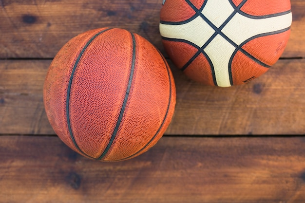 An overhead view of two basketball on wooden textured background