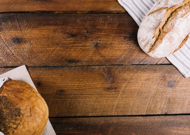 An overhead view of two different type of bread on wooden background