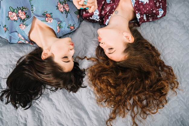 Overhead view of two female friends pouting lips while lying on bed