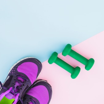An overhead view of two green dumbbells and pair of shoes on dual background