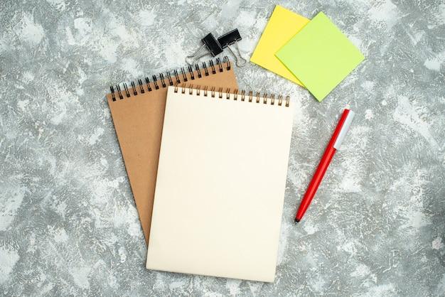 Vista dall'alto di due quaderni a spirale kraft con carte da lettere colorate a penna su sfondo di ghiaccio