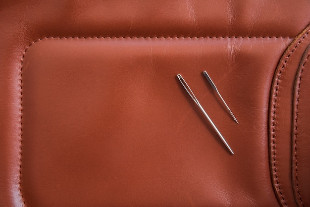 An overhead view of two needles on brown leather