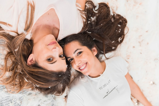 An overhead view of two smiling women lying over soft feathers
