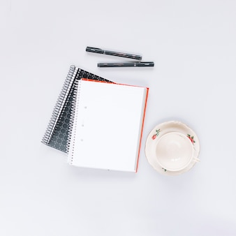 Overhead view of two spiral notebook; pen and empty cup on white background