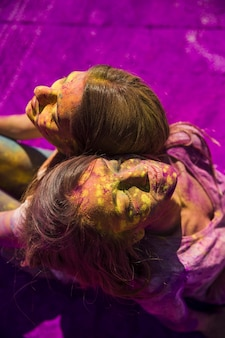 An overhead view of two women sitting back to back with holi color on their face