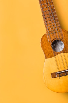 An overhead view of ukulele on yellow background