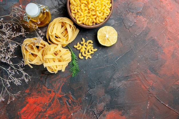 Overhead view of uncooked three spaggeties and green oil bottle on mixed color table