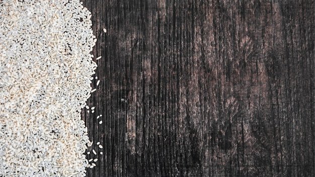 An overhead view of uncooked white rice on black wooden textured backdrop