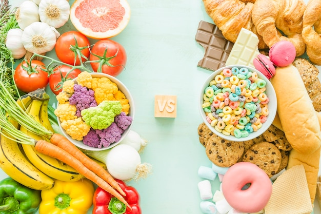 Overhead view of unhealthy versus healthy food over the background