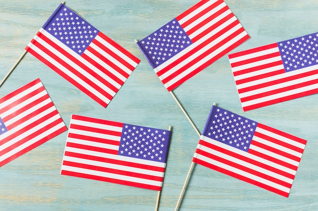 An overhead view of usa flags on blue wooden textured background