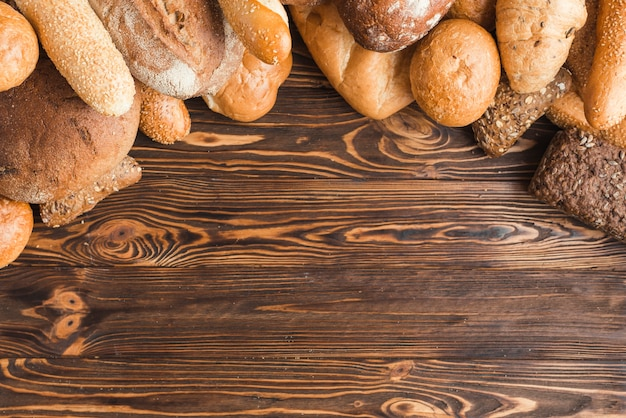 Overhead view of various breads on wooden background