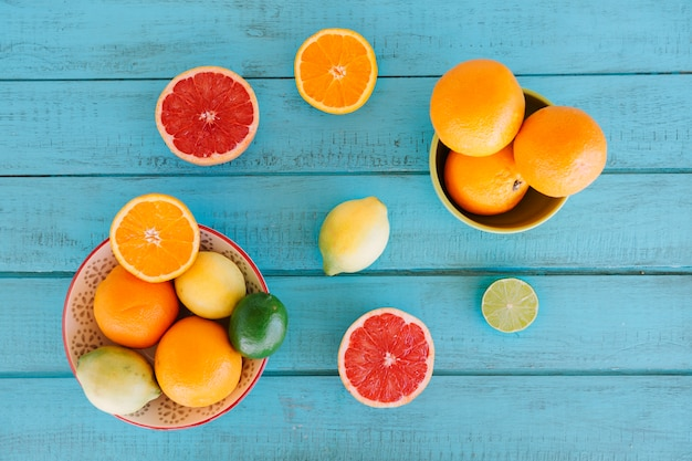 Overhead view of various citrus fruits on blue wooden background