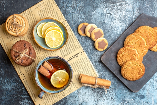 Overhead view of various cookies and a cup of black tea with cinnamon on an old newspaper on dark background
