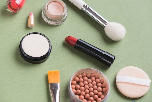 Overhead view of various cosmetic products on green background