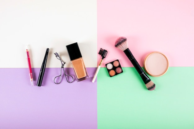 Overhead view of various cosmetic products on multi colored background