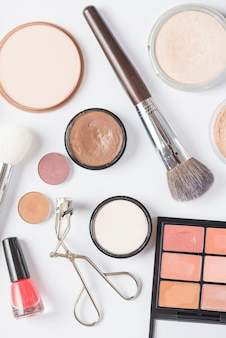 Overhead view of various cosmetic products on white backdrop