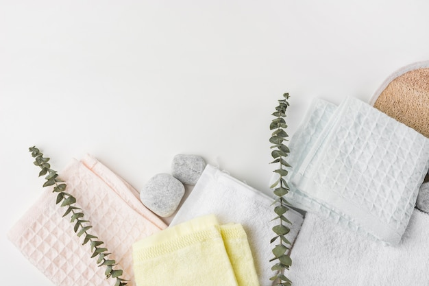 An overhead view of various folded napkins with spa stones and twigs on white background