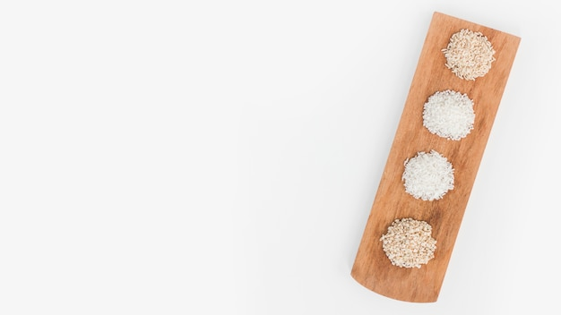 Overhead view of various rice on wooden tray over white surface
