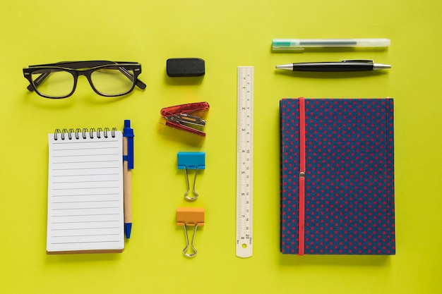 Overhead view of various stationeries on yellow background