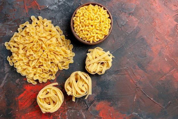 Vista dall'alto di vari tipi di pasta cruda sulla tabella dei colori misti