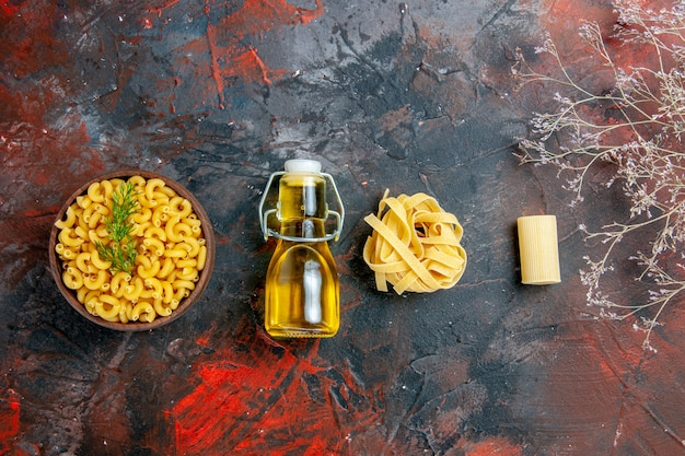 Overhead view of various types of uncooked pastas and oil bottle on mixed color table