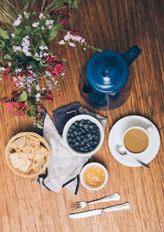 An overhead view of vase; blueberries; crackers; jam; coffee cup and teapot on wooden backdrop