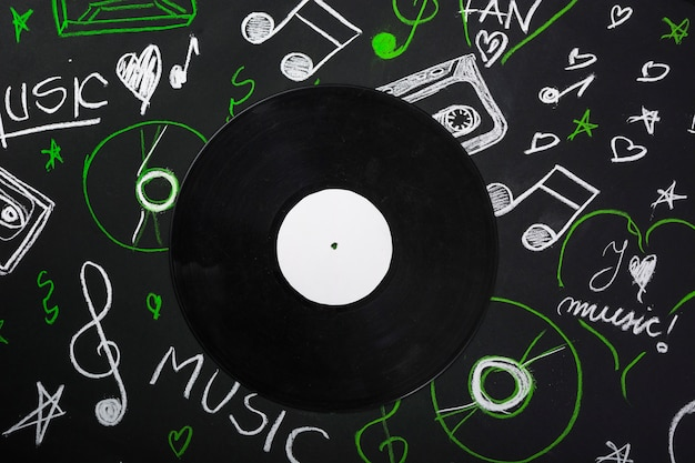 An overhead view of vinyl record over the blackboard with drawn musical notes
