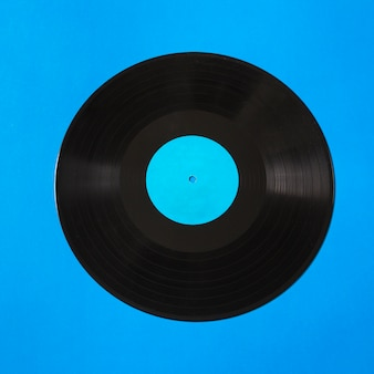 Overhead view of vinyl record on blue background