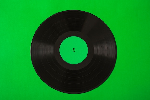 Overhead view of vinyl record on green background