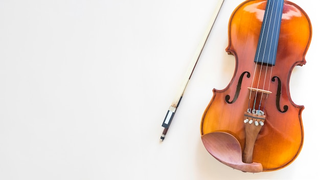 Overhead view of violin with bow on white background