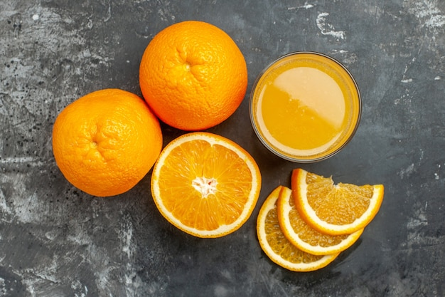 Overhead view of vitamin source cut chopped and whole fresh oranges and juice on gray background