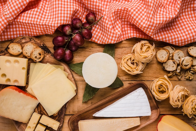 Overhead view of vivid cheese slices and fresh raw food with table cloth