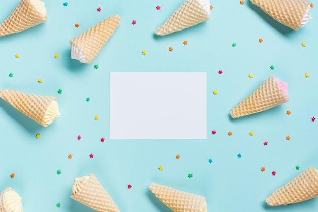 An overhead view of waffle cones and sprinkles surrounded near the white blank paper on blue backdrop