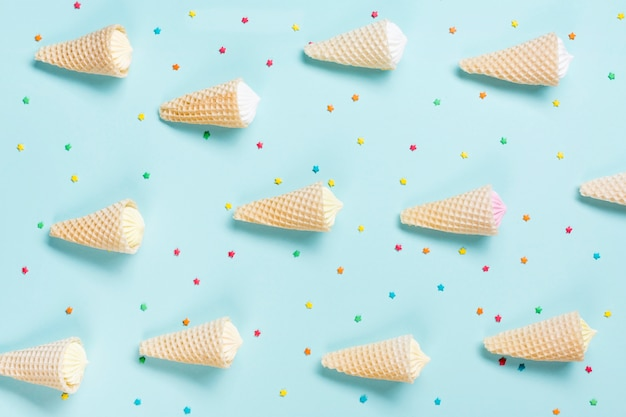 An overhead view of waffle cones with aalaw and sprinkles on blue backdrop