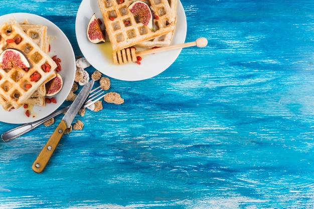 An overhead view of waffles with fig slices on plate against wooden blue textured background