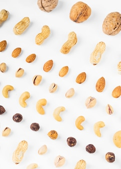 An overhead view of walnuts; peanuts; almonds; pistachios; hazelnut and cashew nuts on white background